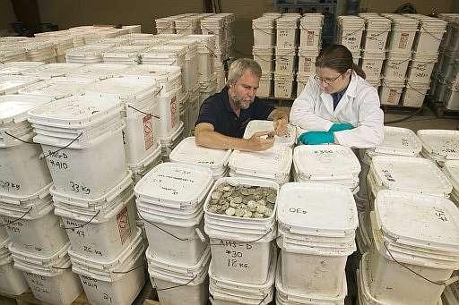 Dos personas examinan las monedas. (Foto: AP)
