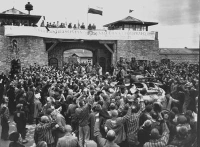 Prisioneros en Mauthausen reciben a las tropas que liberaron el campo en 1945. En la torre, una pancarta de los españoles. / NATIONAL ARCHIVES
