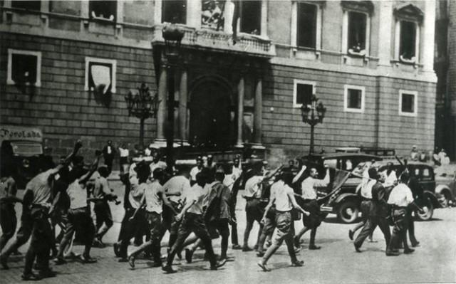 Soldados que han abandonado las filas rebeldes desfilan puño en alto por la plaza de Sant Jaume de Barcelona, el 20 de julio.