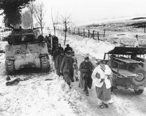 Prisioneros alemanes pasan junto a un Sherman y un jeep Willys durante la batalla de las Ardenas.