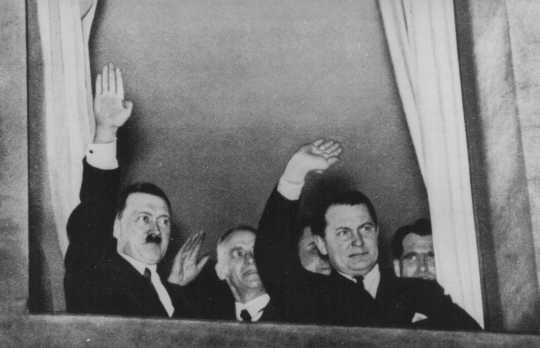 A la derecha, Rudolf Hess en una fotografía de 1933. En versiones posteriores su imagen sería borrada