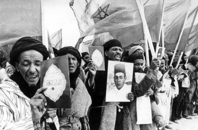 Un grupo de voluntarios marroquíes participantes en la Marcha Verde, muestran retratos del rey Hasan II, textos del Corán y banderas marroquíes. EFE