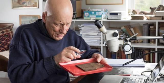 Un investigador revisa una de las tablillsa de madera encontradas. MOLA